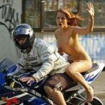 Mulher anda de moto pelada, mas é multada por estar sem capacete